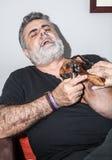 Attraktiver Senior mit dem weißen Bart, der mit Dachshundhund spielt Lizenzfreie Stockfotos