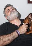 Attraktiver Senior mit dem weißen Bart, der mit Dachshundhund spielt Lizenzfreies Stockfoto