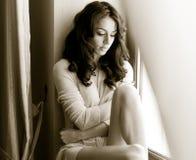 Attraktiver Brunette im weißen Kleid, das provozierend im Fensterrahmen aufwirft Porträt der sinnlichen Frau in der klassisc Lizenzfreie Stockbilder