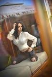 Attraktiver sexy Brunette im weißen festen Sitzhemd und -SCHWARZEM zerriss die Jeans, die provozierend im Fensterrahmen aufwerfen Lizenzfreies Stockbild