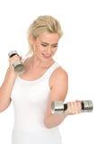 Attraktiver Sitz-gesunde glückliche junge Blondine, die mit stummen Bell-Gewichten ausarbeiten Stockbilder