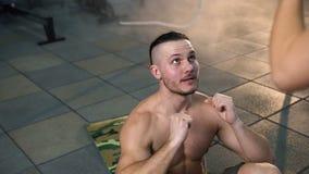 Attraktiver Sportmann, der ABS unter Verwendung des Aerobicballs mit weiblichem Trainer trainieren l?sst stock video