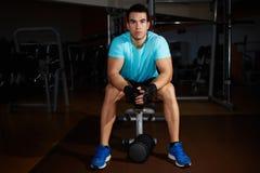 Attraktiver starker Mann, der Pause nach Eignungstraining in der Turnhalle macht Lizenzfreie Stockfotografie