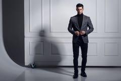 Attraktiver, starker, muskulöser junger Mann kleidete elegant die Klage, die im Studio aufwirft und stand nahe Wand, Schattenhint stockbilder