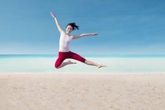 Attraktiver Tänzer, der auf Strand springt Stockbild