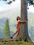Attraktiver Tourist, der den Baum umarmt Stockfoto