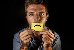 Attraktiver und deprimierter Mann halten Papier mit traurigem Mundabgehobenem betrag des smiley auf seinen schauenden Lippen elen Stockfotos