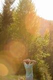 Attraktiver und junger Reisender, der im grünen Wald steht Stockfotografie