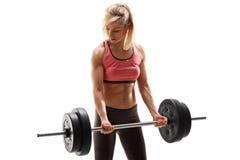 Attraktiver weiblicher Athlet, der mit Barbell trainiert Stockbilder