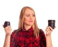 Attraktiver weiblicher Fotograf, der die Linse - lokalisiert auf Weiß wählt Lizenzfreies Stockbild