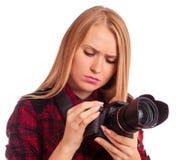 Attraktiver weiblicher Fotograf, der ihre Berufskamera studiert Stockfotografie