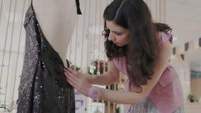 Attraktiver weiblicher Modedesigner bei der Arbeit Schwarzes Glättungskleid mit glänzenden Pailletten auf Mannequin Näherin schni stock footage
