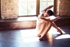 Attraktiver weiblicher Tänzer, der auf dem Boden sitzt stockfotografie