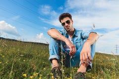 Attraktiver zufälliger Mann mit den Gläsern, die in einer Rasenfläche stillstehen Lizenzfreies Stockfoto