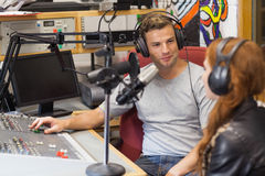 Attraktiver zufriedener Radiowirt, der einen Gast interviewt Stockbild
