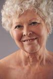Attraktives älteres Frauengesicht mit einem süßen Lächeln Stockbild