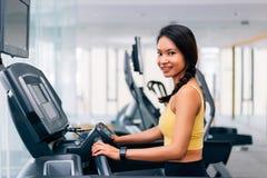 Attraktives Asiatinlächeln und -betrieb auf einer laufenden Tretmühle an der Turnhalle stockfoto