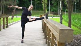 Attraktives athletisches Mädchen, das Übungen für das Ausdehnen von Beinen tut Langsame Bewegung stock video footage