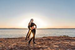 Attraktives athletisches Mädchen, welches die Stellung auf einem sandigen Strand in den Strahlen der untergehenden Sonne aufwirft Lizenzfreies Stockfoto
