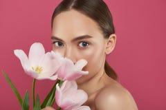 Attraktives Bedeckungsgesicht der jungen Frau mit schönen Tulpen lizenzfreie stockfotos