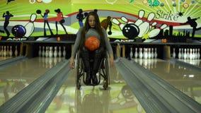 Attraktives behindertes Mädchen in einem Rollstuhl, der Spaß im Bowlingspiel, bewegend durch die Bowlingspiellinie hat stock video