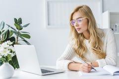 attraktives blondes Geschäftsfrau Schreiben und workig mit Laptop im modernen Licht Stockfoto