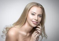 Attraktives blondes lächelndes Frauenporträt auf grauem Hintergrund Lizenzfreies Stockbild