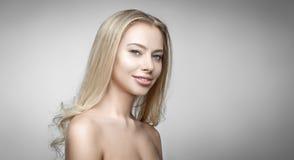 Attraktives blondes lächelndes Frauenporträt auf grauem Hintergrund Stockfotos