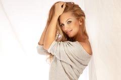 Attraktives blondes lächelndes Frauenporträt auf weißem Hintergrund Lizenzfreie Stockfotografie