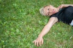 Attraktives blondes Lügen auf dem Gras Lizenzfreies Stockfoto