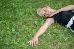 Attraktives blondes Lügen auf dem Gras Lizenzfreie Stockfotos