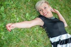 Attraktives blondes Lügen auf dem Gras Lizenzfreie Stockbilder