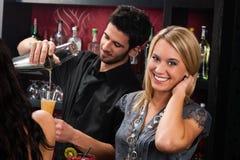 Attraktives blondes Mädchen am Cocktailstablächeln Stockbilder