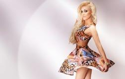 Attraktives blondes Mädchen, das über den hellen Hintergrund tanzt. Stockfotos