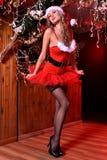 Attraktives blondes Mädchen, das als sexy Santa Helper aufwirft Stockfotos