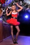 Attraktives blondes Mädchen, das als sexy Santa Helper aufwirft Stockbild