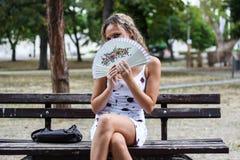 Attraktives blondes Mädchen, das auf der Bank in einem Park und in einem Verstecken sitzt Lizenzfreies Stockbild