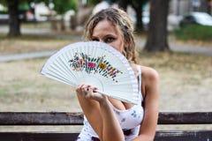 Attraktives blondes Mädchen, das auf der Bank in einem Park und in einem Verstecken sitzt Stockbild