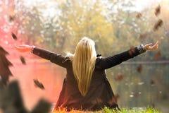 Attraktives blondes Mädchen, das einen Park im Herbst genießt Lizenzfreie Stockbilder