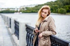 Attraktives blondes Mädchen, das entlang die Promenade geht und Musik mit Kopfhörern hört Lizenzfreie Stockfotografie