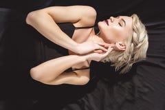 attraktives blondes Mädchen, das im schwarzen Kleid aufwirft Stockfotos