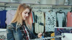 Attraktives blondes Mädchen, das Kleidung im Mall wählt stock footage