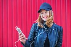 Attraktives blondes Mädchen, das Musik auf seinem Smartphone hört Stockfotos