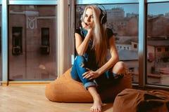 Attraktives blondes Mädchen, das Musik in den Kopfhörern hört und Stockfotografie