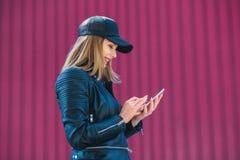 Attraktives blondes Mädchen in der ledernen schwarzen Jacke und in der Kappe, das Internet an einem Handy surfend Stockbilder