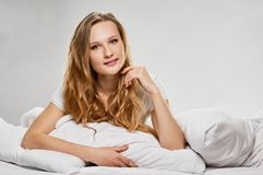 Attraktives blondes Mädchen im Bett Stockbilder