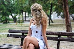 Attraktives blondes Mädchen mit dem gelockten Haar, das auf der Bank in a sitzt Stockbild