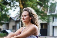 Attraktives blondes Mädchen mit dem gelockten Haar, das auf der Bank in a sitzt Lizenzfreie Stockfotos