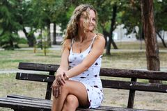 Attraktives blondes Mädchen mit dem gelockten Haar, das auf der Bank in a sitzt Lizenzfreies Stockfoto