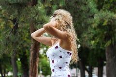Attraktives blondes Mädchen mit dem gelockten Haar in einem Park, der mit ihm spielt Stockfoto